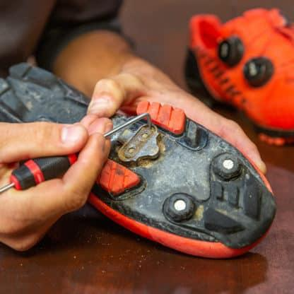 mechanic using pick to remove mud from shoe