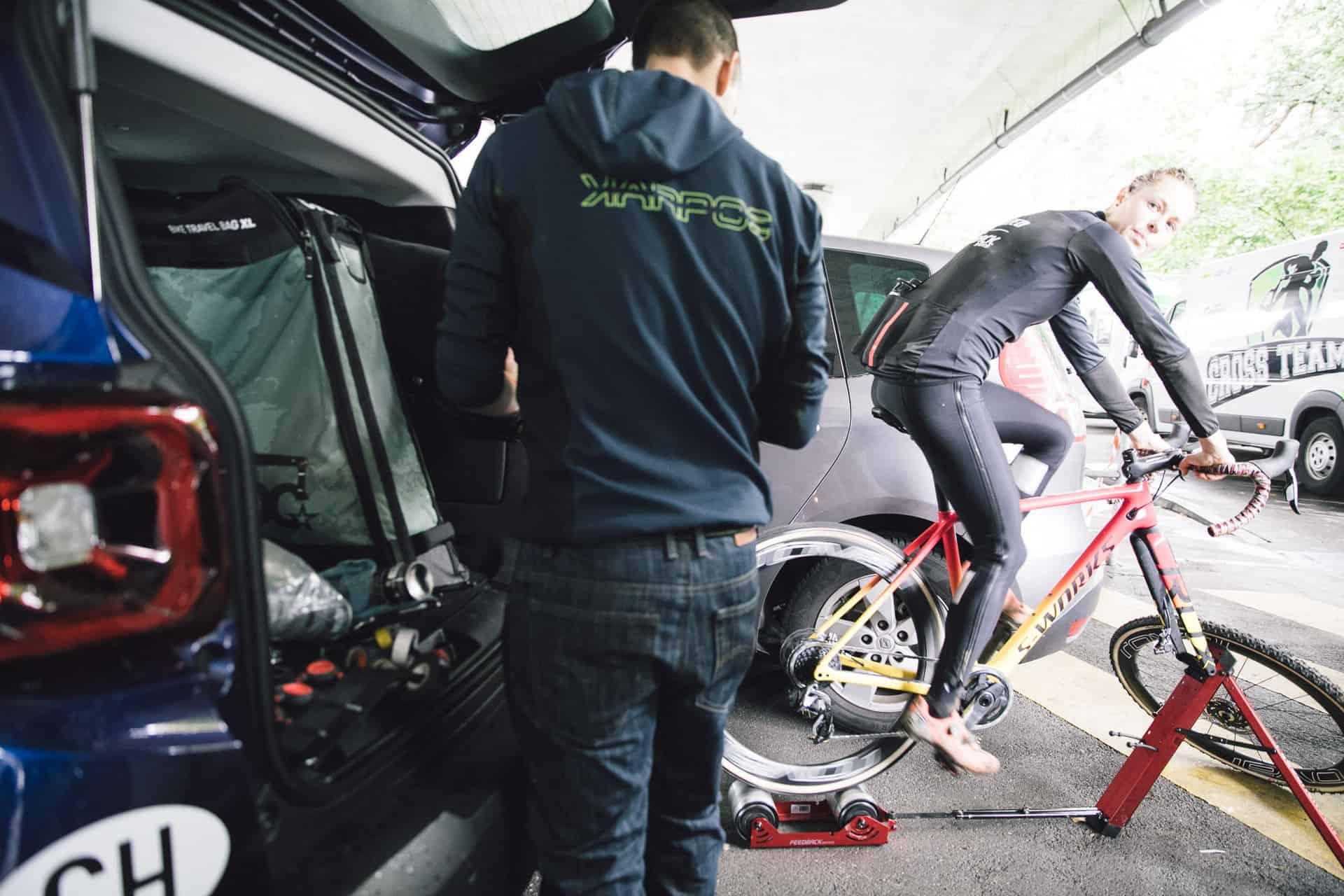 mechanic working on bike while cyclist rides