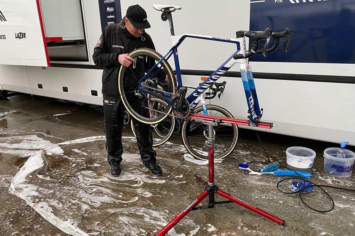 man outside working on road bike mounted to repair stand