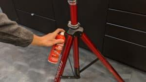 man spraying dry bike lubricant on repair stand