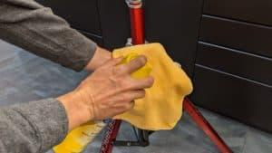 man spraying pledge multisurface polish on clean rag to wipe down repair stand frame