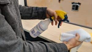man spraying isopropyl alcohol on a clean rag