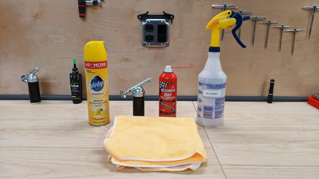 Pledge, Bike polish, Grease Spray Lubricant, Isopropyl Alcohol, and several clean rags on work bench